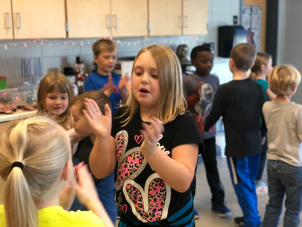A student claps along with a dance to Jingle Bells