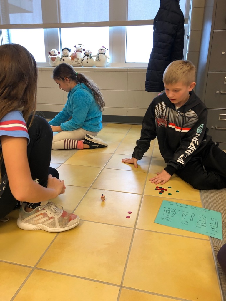 Students play the dreidel game