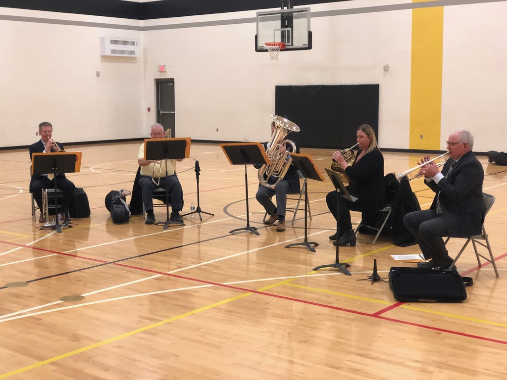 A brass quintet plays for students